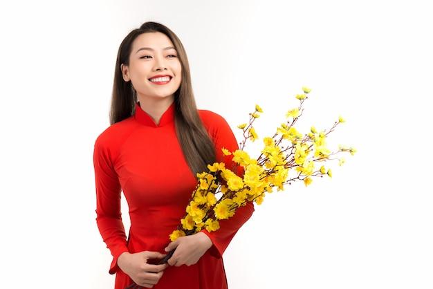 Belle femme asiatique portant la traditionnelle ao dai du vietnam tenant une fleur de pêcher pendant les vacances du têt.
