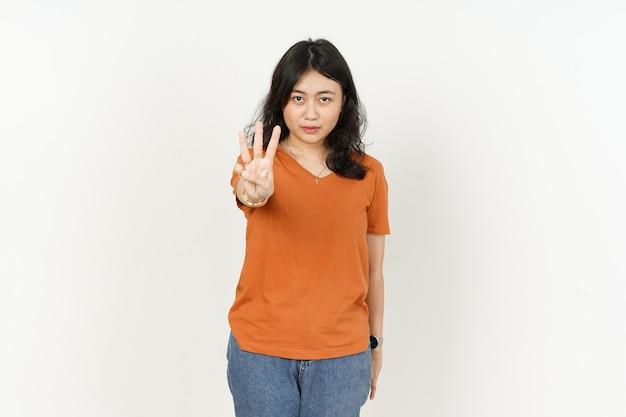 Belle femme asiatique portant un tshirt de couleur orange montrant trois doigts isolé sur fond blanc