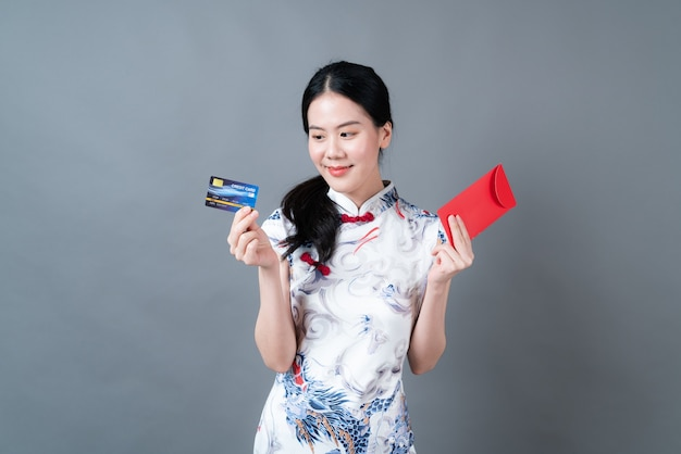 Une belle femme asiatique porte une robe traditionnelle chinoise avec une enveloppe rouge ou un paquet rouge et une carte de crédit sur fond gris