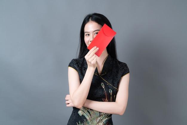Belle femme asiatique porte une robe traditionnelle chinoise avec enveloppe rouge ou paquet rouge