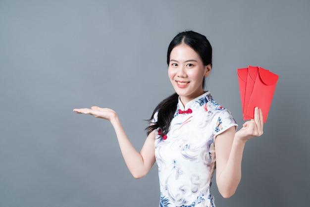 Une belle femme asiatique porte une robe traditionnelle chinoise avec une enveloppe rouge ou un paquet rouge