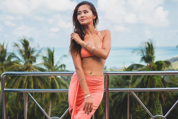 Belle femme asiatique posant en maillot de bain bikini rose et paréo sur la terrasse sur la villa tropicale souriant heureux en vacances à thailnad, style été corps sexy