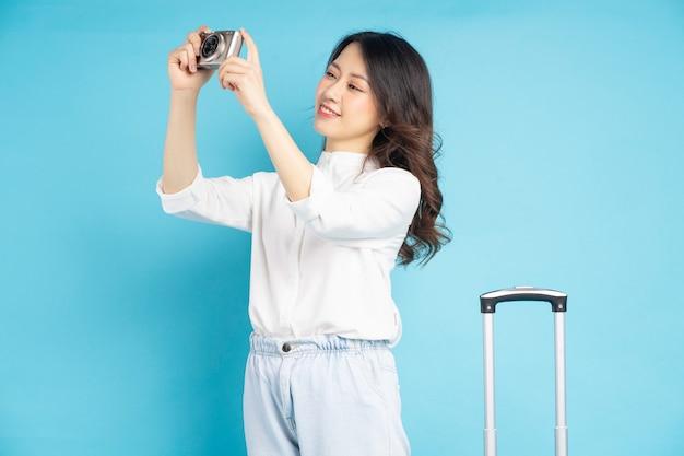 Belle femme asiatique prenant une photo avec une valise à côté d'elle