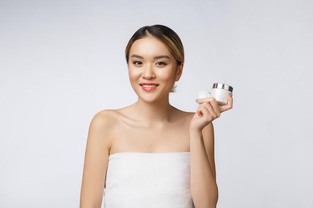 Belle femme asiatique présentant le produit isolé sur fond blanc.