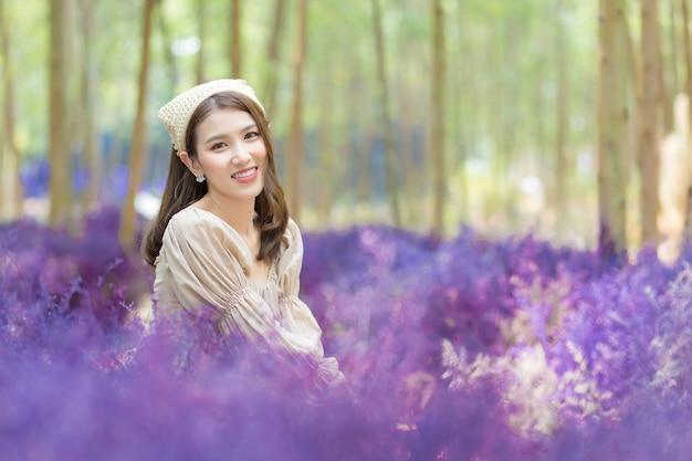 Une belle femme asiatique qui porte une robe est assise dans un jardin de fleurs violettes et sourit joyeusement.