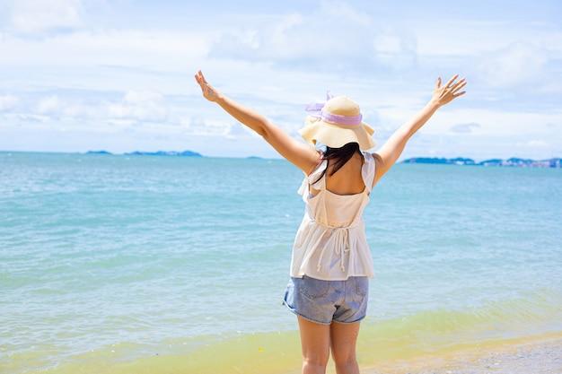 Belle femme asiatique relaxante se sentant heureuse à la plage