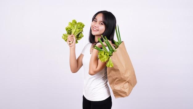 Belle femme asiatique avec sac en papier de légumes frais et tenant de la laitue fraîche avec une surface blanche isolée