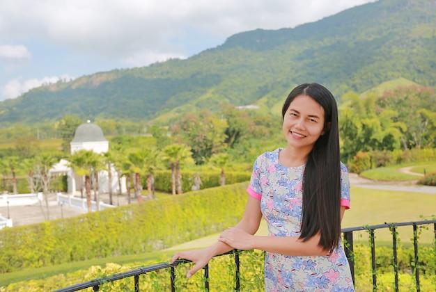 Belle femme asiatique se détendre sur un balcon à flanc de colline avec regarder la caméra.