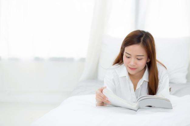 Belle femme asiatique se détendre mentir livre de lecture sur la chambre