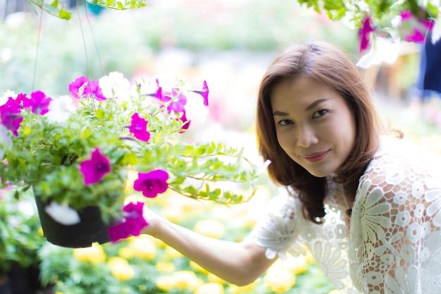Belle femme asiatique sélectionnant la fleur dans le magasin floral, mode de vie de la femme au foyer moderne.