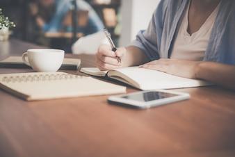 Belle femme asiatique souriante et écrit un cahier sur la table