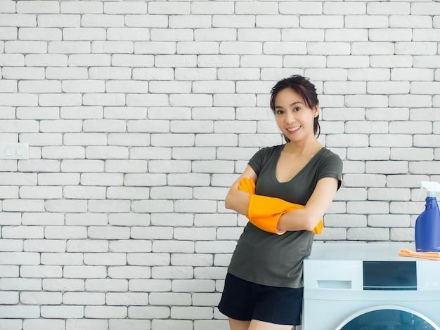 Belle femme asiatique souriante, femme au foyer heureuse portant des gants de protection en caoutchouc orange debout avec les bras croisés à côté de la machine à laver sur le mur de briques blanches