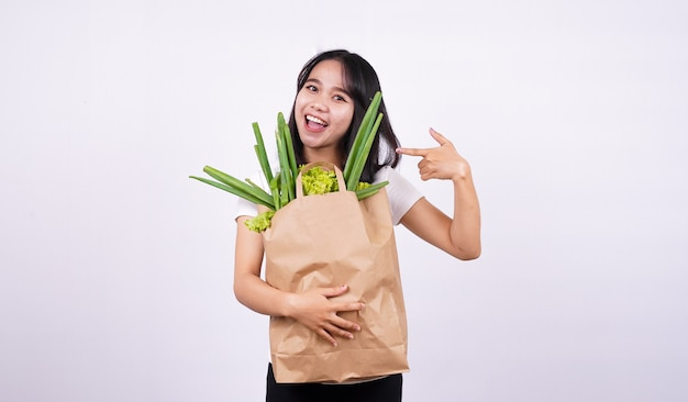 Belle femme asiatique souriante avec sac en papier de légumes frais avec surface blanche isolée