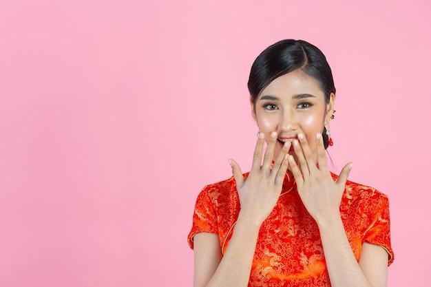 Belle femme asiatique sourire heureux et se sentir excité au nouvel an chinois sur fond rose.