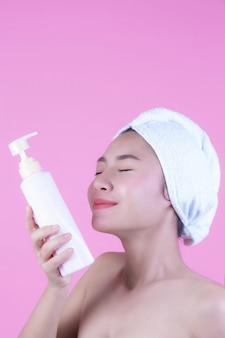 Belle femme asiatique tenant une bouteille de produit sur un fond rose.