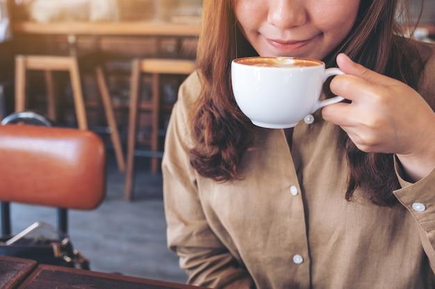 Une belle femme asiatique tenant et buvant du café chaud avec se sentir bien au café