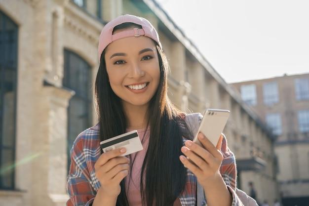 Belle femme asiatique tenant une carte de crédit, achats en ligne