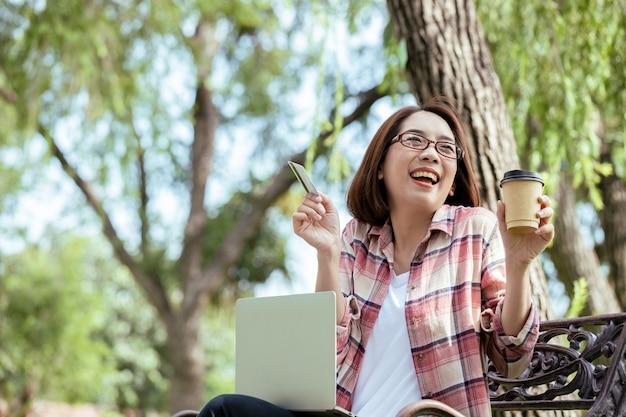 Belle femme asiatique tenant une carte de crédit avec une tasse de café pour manger du café, montrer le visage souriant de rire
