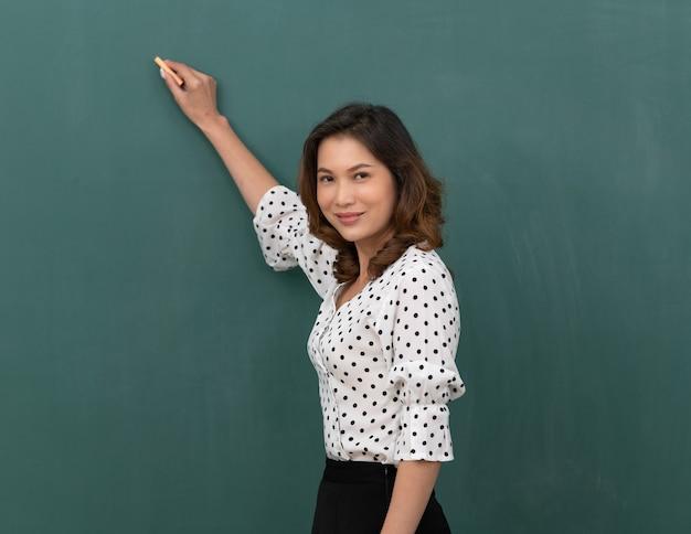 Belle femme asiatique tenant une craie debout devant un tableau noir avec espace de copie.