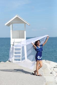 Belle femme asiatique tenant un drap blanc et profiter de vacances sur la plage