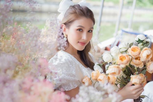 Belle femme asiatique tenant des fleurs avec fond naturel.