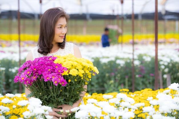 Belle femme asiatique tenant des fleurs jaunes dans les mains avec fierté, propriétaire de jardin fleuri satisfait de fleurs de bonne qualité à vendre.