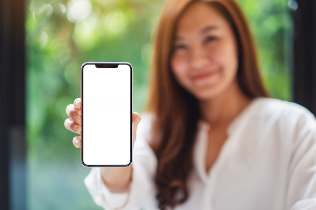 D'une belle femme asiatique tenant et montrant un téléphone mobile avec écran blanc vierge, nature verte floue