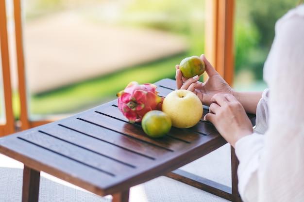 Une belle femme asiatique tenant une orange avec poire et fruit du dragon sur une petite table en bois