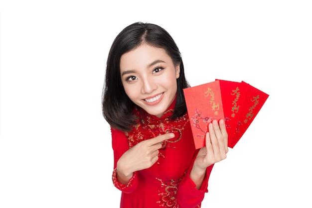 Belle femme asiatique tenant une poche rouge - argent chanceux. vacances du têt. nouvelle année lunaire. texte signifie bonheur et chance