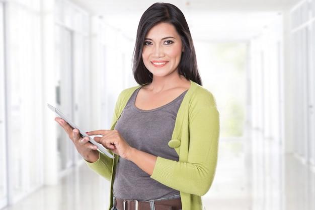 Belle femme asiatique tenant une tablette à écran tactile numérique