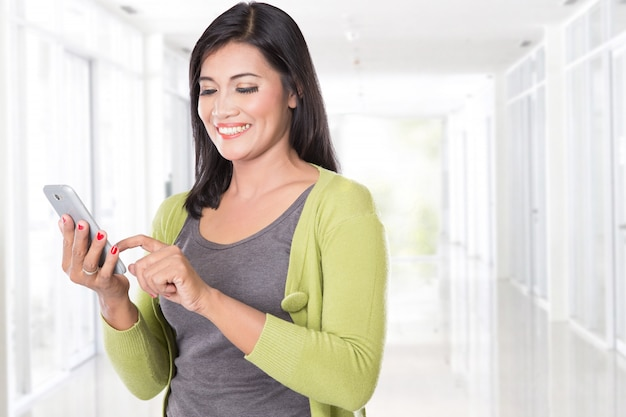 Belle femme asiatique tenant un téléphone portable