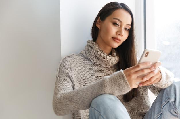 Belle femme asiatique en train de taper sur un téléphone portable assis sur le rebord de la fenêtre à l'intérieur