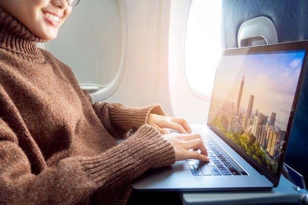 Belle femme asiatique travaille avec un ordinateur portable en avion