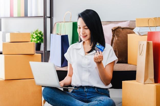 Belle femme asiatique utilisant un ordinateur portable avec des achats par carte de crédit en ligne à la maison