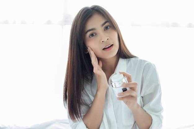Une belle femme asiatique utilisant un produit de soin de la peau, une crème hydratante ou une lotion en prenant soin de son teint sec. crème hydratante dans les mains des femmes.