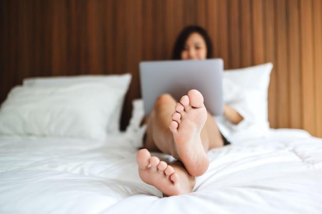 Une belle femme asiatique utilisant et travaillant sur un ordinateur portable en position couchée sur un lit confortable blanc à la maison