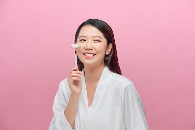 Belle femme asiatique utilise un rouleau de jade pour masser son visage