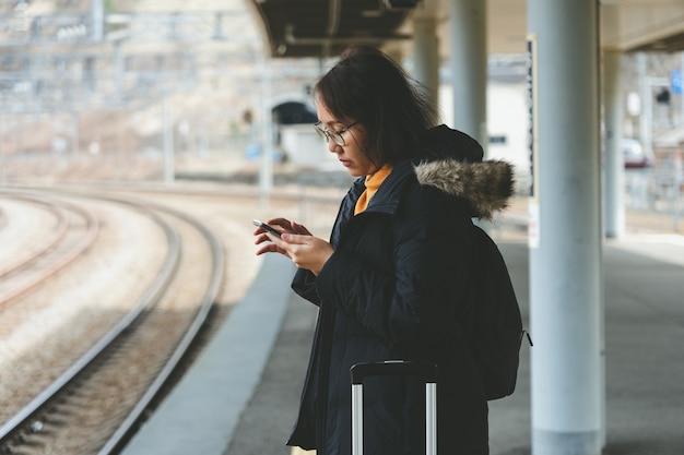 Une belle femme asiatique utilise un smartphone dans le centre-ville pour rechercher