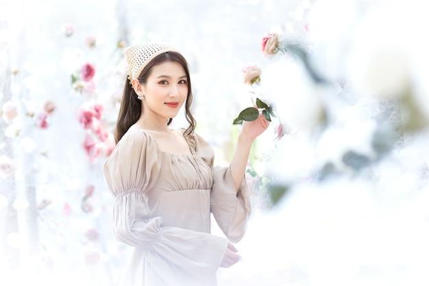 Belle femme asiatique vêtue d'une robe crème sourit et se tient dans un jardin de fleurs de roses blanches comme naturelles