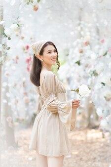 Belle femme asiatique vêtue d'une robe crème sourit et se tient dans un jardin de fleurs de roses blanches comme thème naturel et luxueux