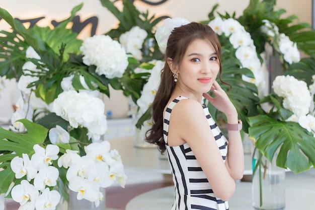 Une belle femme asiatique vêtue d'une robe rayée noire et blanche est debout souriante au milieu d'orchidées blanches