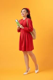 Belle femme asiatique vêtue d'une robe rouge et debout sur un fond orange