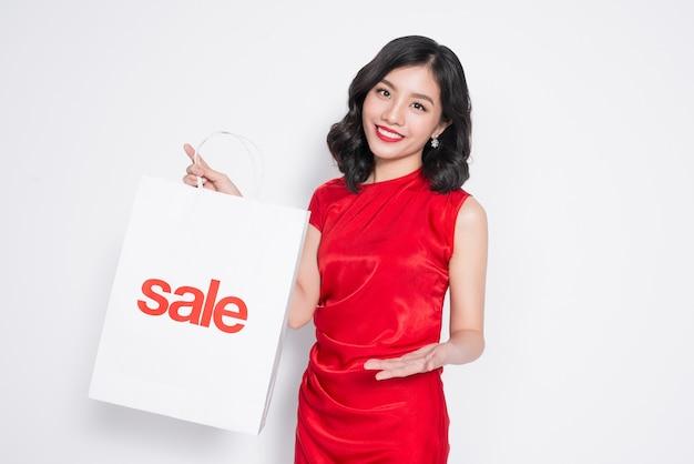 Belle femme asiatique vêtue d'une robe rouge avec panier debout sur blanc.
