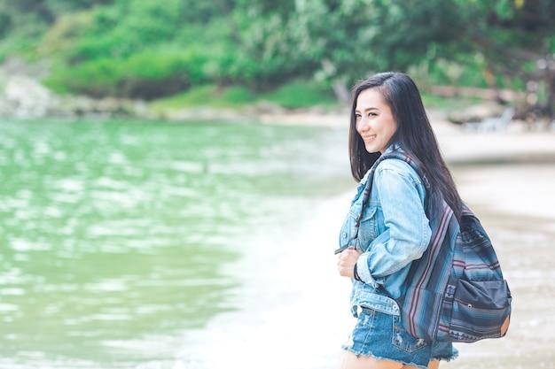 Belle femme asiatique voyageur avec un sac à dos debout sur la plage.