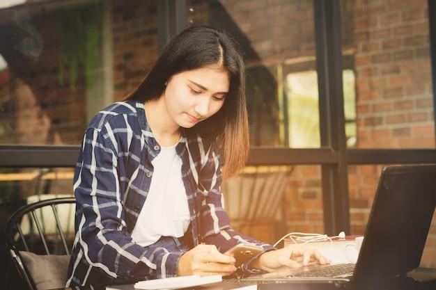 Belle femme d'asie à l'aide d'ordinateur et de téléphone mobile travaillant avec heureux
