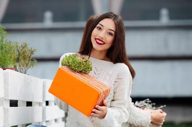 Belle femme assise sur un banc et tenant dans ses mains un cadeau