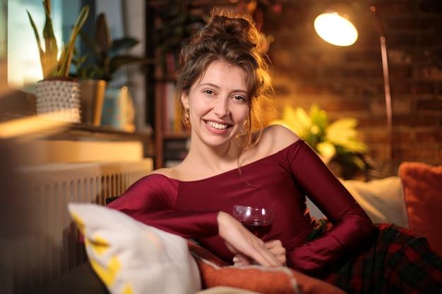 Belle femme assise sur le canapé, célébrant quelque chose tout en prenant un verre de vin rouge