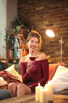 Belle femme assise sur le canapé, célébrant avec un verre de vin rouge - jeune femme élevant des vêtements élégants