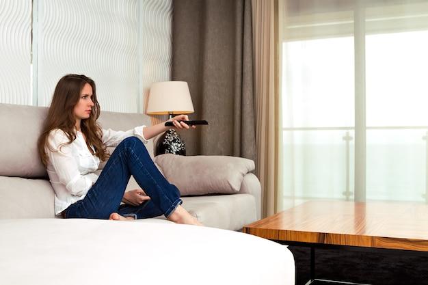 Belle femme assise sur un canapé à l'intérieur et tenant une télécommande de télévision dans sa main