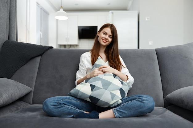 Belle femme assise sur un canapé avec oreiller jambes pliées dans les mains confort dans un appartement.